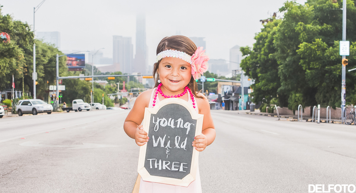 young wild and three chalk sign birthday third austin texas soco south congress portrait child children portraiture photographer pink balloon balloons