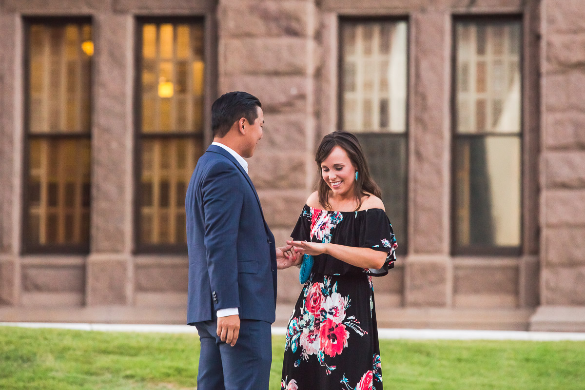 newly engaged couple admiring ring austin texas state capitol