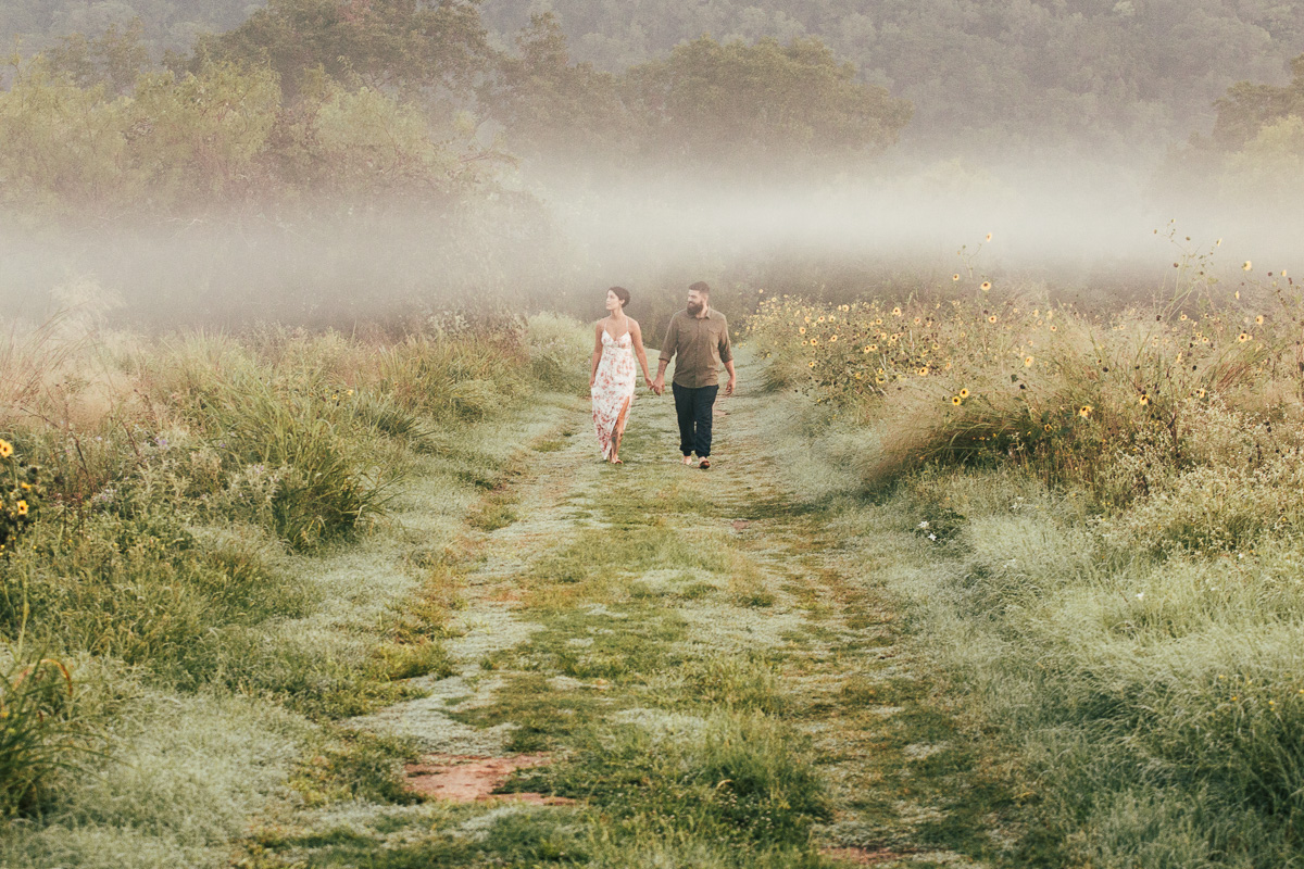 Misty morning wedding engagement portrait of young couple holding hands walking on a dewy sunflower strewn grass trail in praire ranch Austin Texas