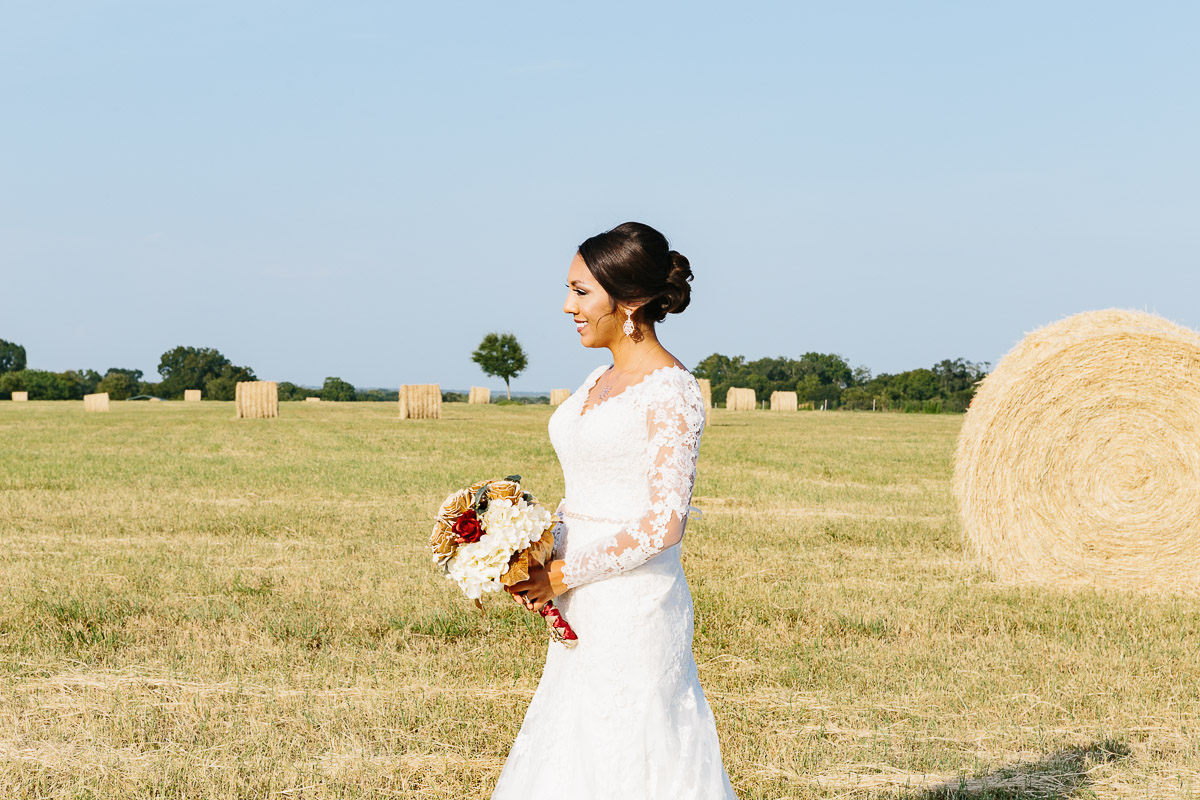 bride standing in field hay bales eberly ranch
