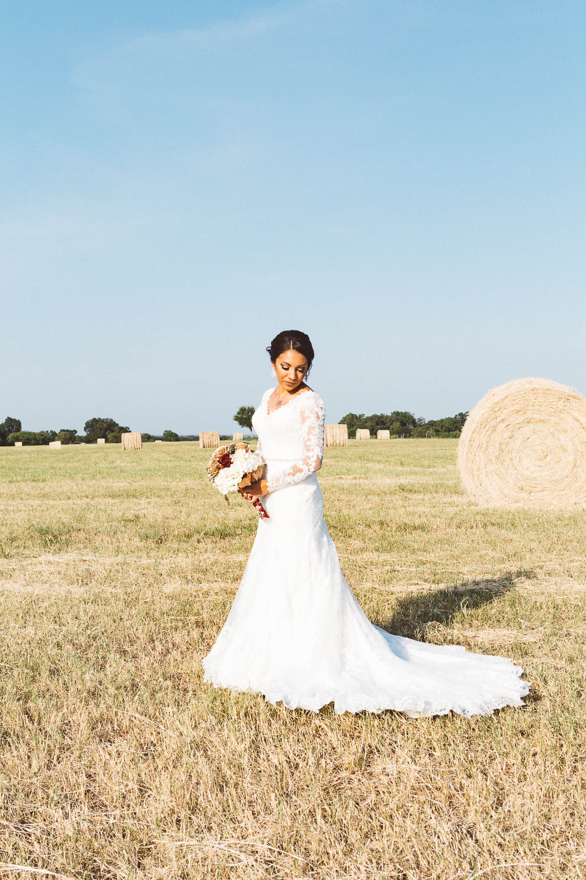 bride standing in field with hay bales Chappell Hill Texas