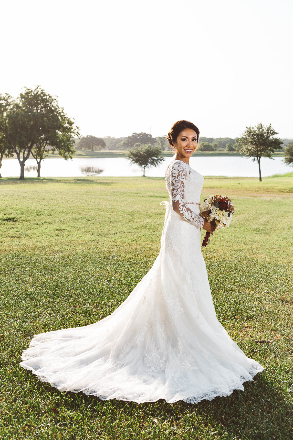 bride standing by lake eberly ranch texas